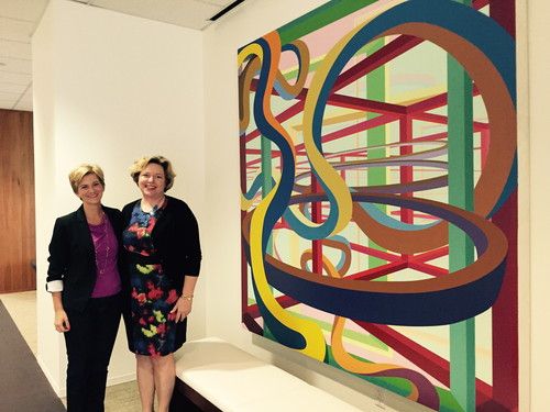 Brooks McCorcle, president (right) and Sue Galvanek, VP - Marketing, Pricing and Product Solutions, pose at the AT&T Partner Solutions office in Plano, alongside artwork McCorcle specifically brought in from AT&T's collection. The painting, Vorcex III by Al Held, had hung in the St. Louis office of the former Southwestern Bell, where McCorcle began her career. Throughout the AT&T Partner Solutions space, artwork is used for inspiration and diversion.