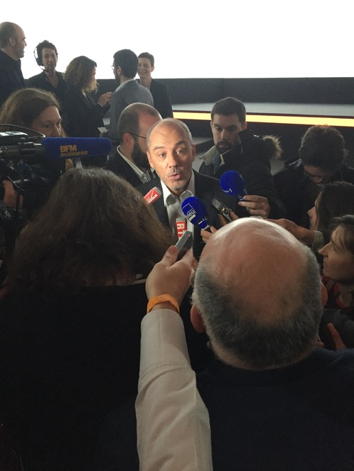 Orange CEO Stephane Richard being mobbed by reporters.