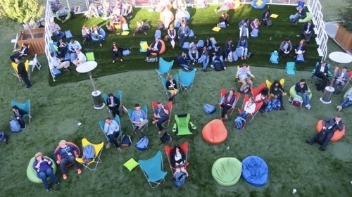 Attendees relax on a fake grass lawn laid out on a San Francisco street near the Moscone Center.