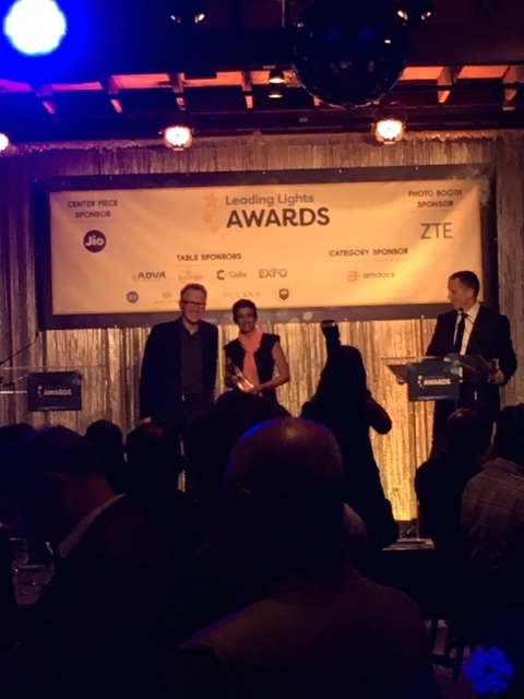 Nextleaf's Nithya Ramanathan accepts her award from Light Reading's Ray Le Maistre as the paparazzi and audience looks on.