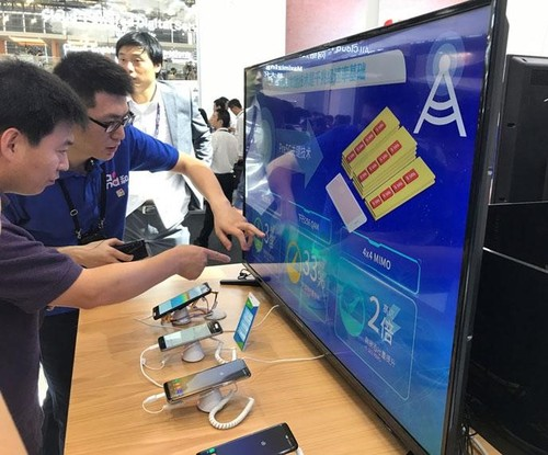 China Mobile booth visitor observing the Gigabit LTE demo with the Samsung Galaxy S8, and getting an explanation of the three technologies underlying Gigabit LTE: carrier aggregation, 4x4 MIMO and 256-QAM.