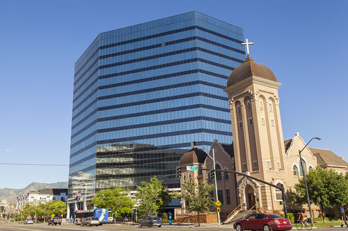 CenturyLink's modern building in Salt Lake City alongside historic church