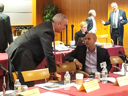 Google's John Burchett (seated) holds a side conversation during a break in the BDAC meeting.