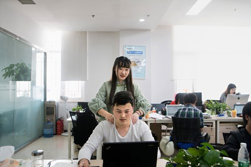 'Shen Yue, who has a degree in civil engineering, giving a colleague a massage in her role as a 'programmer motivator' at Chainfin.com in Beijing,' an article in The New York Times states.