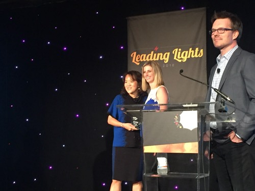 AT&T's Anne Chow receives her award for Most Inspiring Woman of the Year from WiC Director Sarah Thomas, while Light Reading's Phil Harvey basks in the inspiring glow.