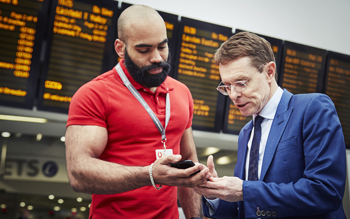 Extravagantly muscled Vodafone operative runs Andy Street, the Mayor of the West Midlands, through the benefits of 5G at Birmingham New Street Station.