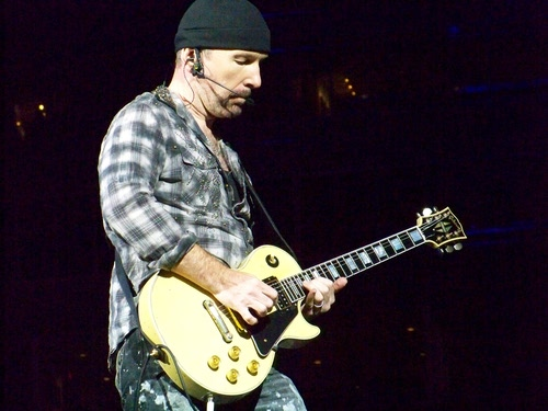 Beanie-wearing U2 guitarist 'The Edge' performs in concert.