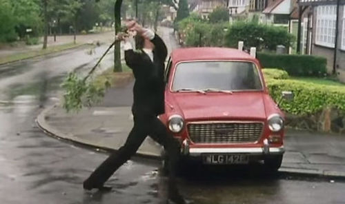 Basil Fawlty, played by John Cleese, gives his broken-down car a damn good thrashing.