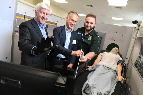 Gerry McQuade, CEO of BT Enterprise, wears the haptic glove while Fotis Karonis, BT 5G executive advisor, and Cameron McVittie, operations manager at West Midlands Ambulance Service, have fun with the scanner.