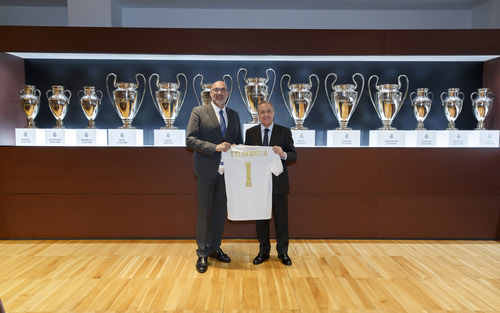 Real Madrid's Florentino Perez (left) and Telefonica Espana's Emilio Gayo grapple over who gets the Los Galacticos' No. 1 shirt in front of a frankly showy-offy amount of silverware.