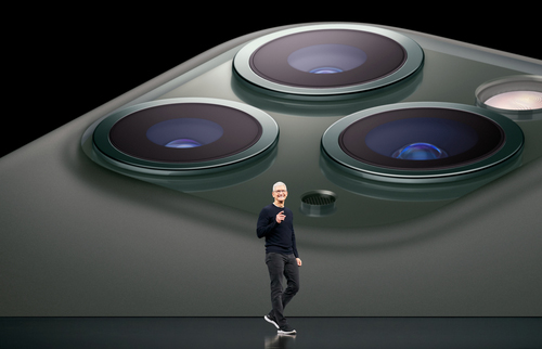 Apple CEO Tim Cook in front of  a huuuuuuuge photo of the iPhone 11's multiple camera lenses.