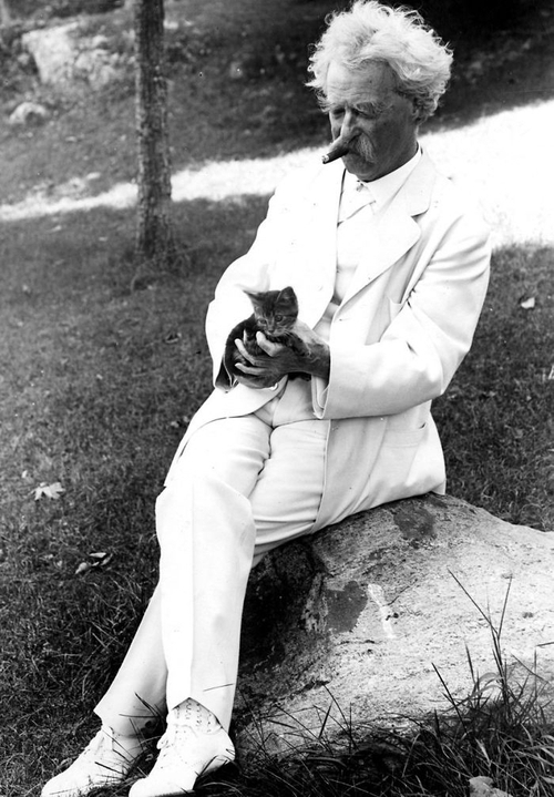 Mark Twain, who survived rumors of his death, enjoys a smoke with a friend.