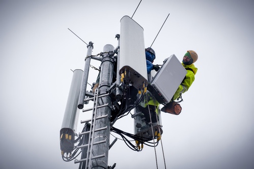 A Deutsche Telekom engineer joyfully erects an antenna.