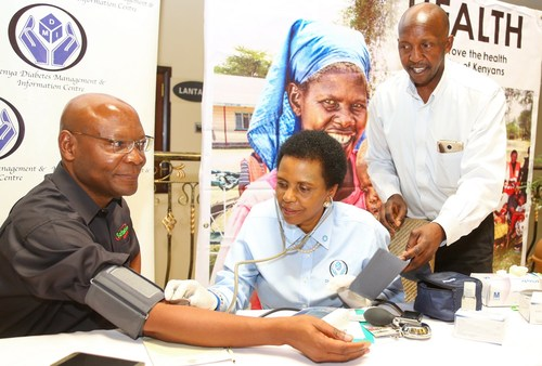 Joseph Ogutu, Chairman of the Safaricom Foundation, has his blood pressure checked by Eva Muchemi, Executive Director at the Kenya Diabetes Management and Information Center, during the Safaricom Mt. Kenya region dissemination forum at the White Rhino Hotel. Looking on is Joseph Mwangi, Health Coordinator, DMI.