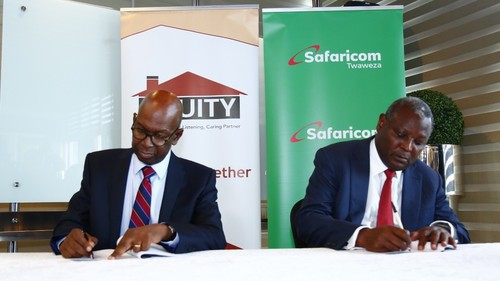 Bob Collymore (left) and Dr. James Mwangi (right) sign the agreement between Equity Group and Safaricom.