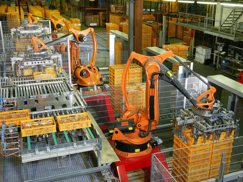 Factory automation: Industrial robots palletizing food products including bread and toast at a bakery in Germany.