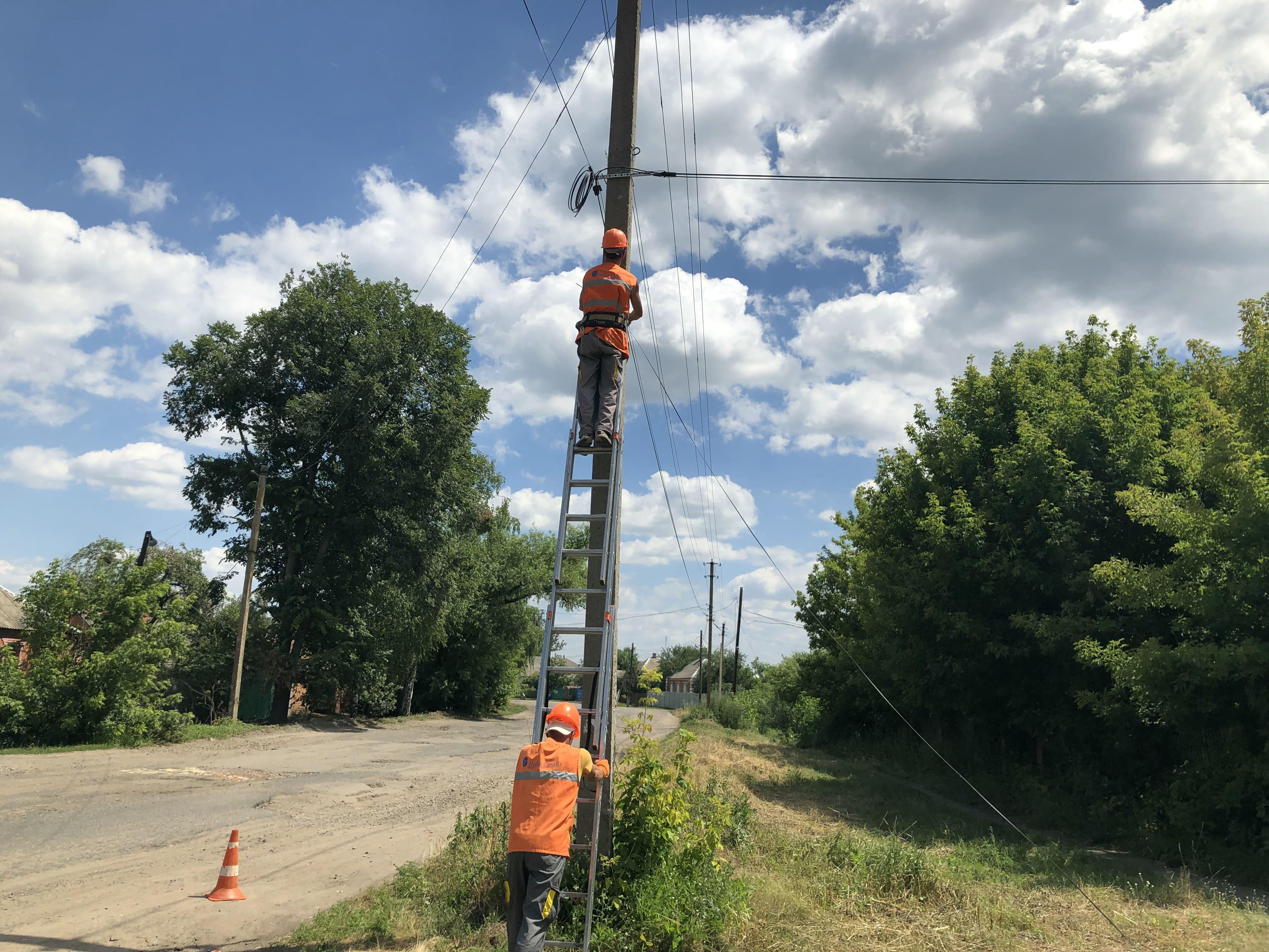 Ukrtelecom engineers rolling out overhead broadband cables.  (Source: Ukrtelecom)